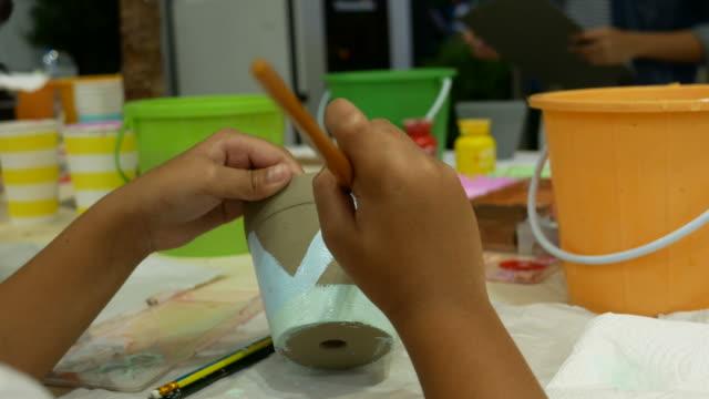 vídeos de stock e filmes b-roll de girl painting with brush - edifício de infantário