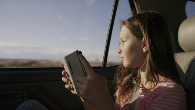 Girl passenger in car reading digital tablet / Hanksville, Utah, United States