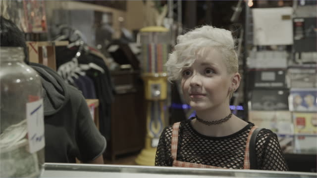 vídeos de stock e filmes b-roll de girl paying for merchandise with credit card in music store / provo, utah, united states - empregado de balcão