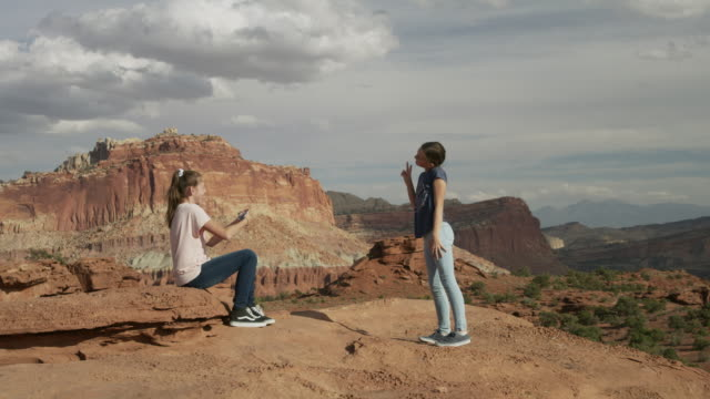 girl photographing friend in scenic view of desert landscape with cell phone / capitol reef national park, utah, united states - braun stock-videos und b-roll-filmmaterial