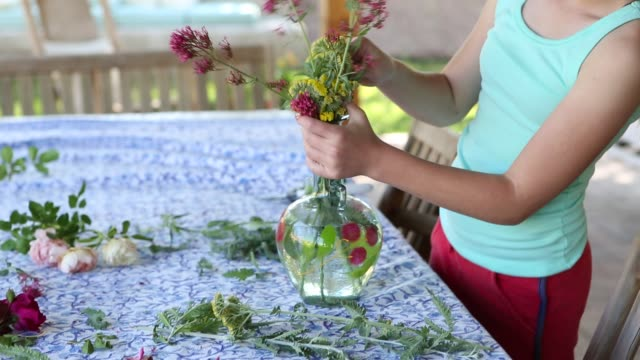 girl picking and arranging flowers from her garden - maglietta senza maniche video stock e b–roll