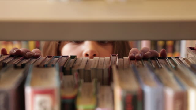 CU Girl picking book from bookshelf / Flagstaff, Arizona, USA