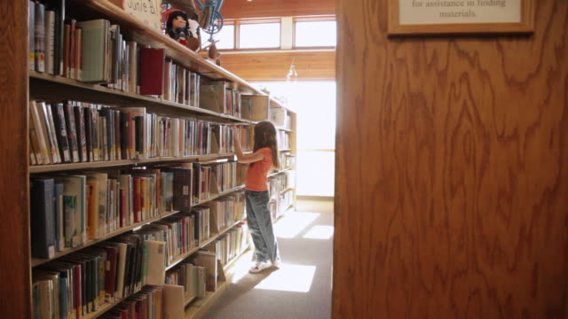 ws pan girl picking books from bookshelf at library / flagstaff, arizona, usa - one girl only stock videos & royalty-free footage