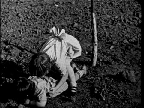 B/W 1927 girl picking other child up from ground in lemon orchard outdoors / educational