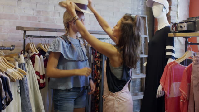 girl placing hat onto head of friend in clothing store / provo, utah, united states - putting stock videos & royalty-free footage