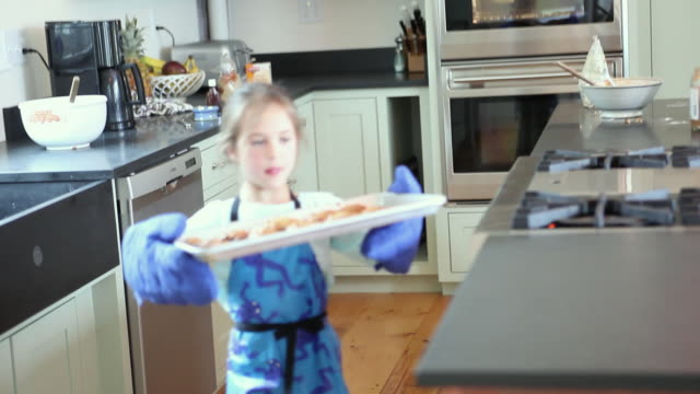 ms focusing girl (6-7) placing hot baking sheet with cookies on kitchen counter, yarmouth, maine, usa - oven mitt stock videos and b-roll footage