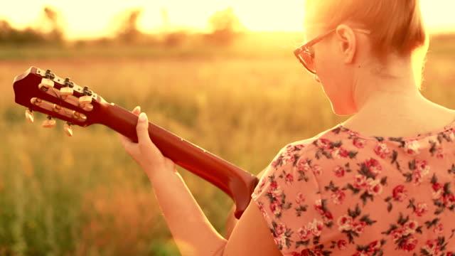 vídeos y material grabado en eventos de stock de niña tocando la guitarra en la naturaleza - diseño floral