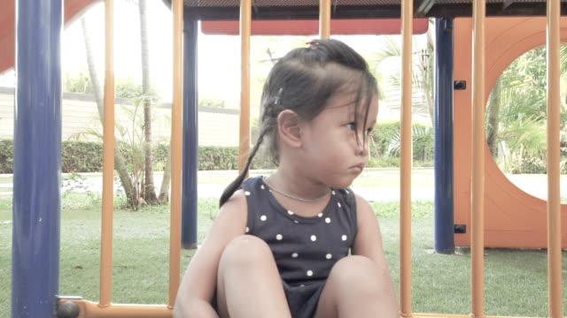 Une fille jouant seule à l'aire de jeux