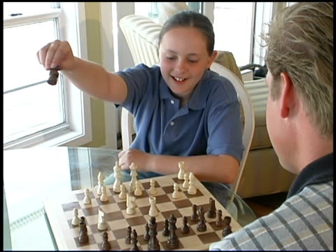 stockvideo's en b-roll-footage met girl playing chess with father - spelletjesavond