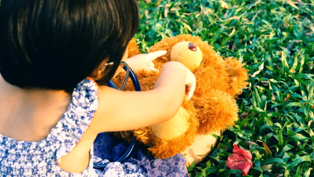 Girl Playing Doctor with Bear in the garden