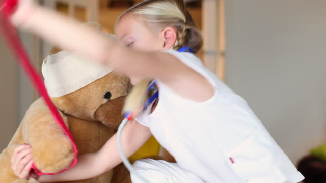 MS Girl (4-5) playing doctor with teddy bear in living room / Brussels, Brabant, Belgium