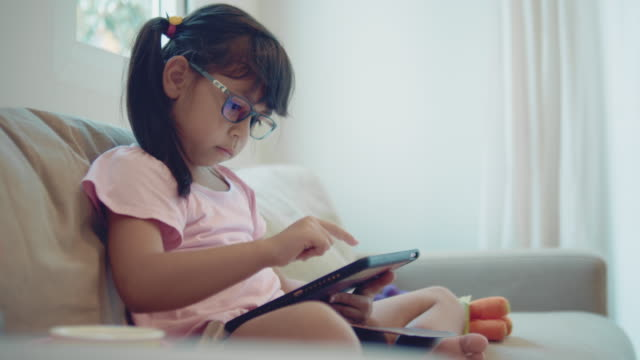 girl playing game on tablet - child sitting cross legged stock videos & royalty-free footage