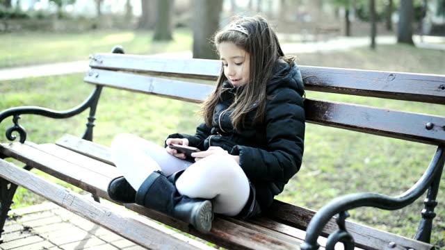 vidéos et rushes de fille jouant des jeux - assis en tailleur