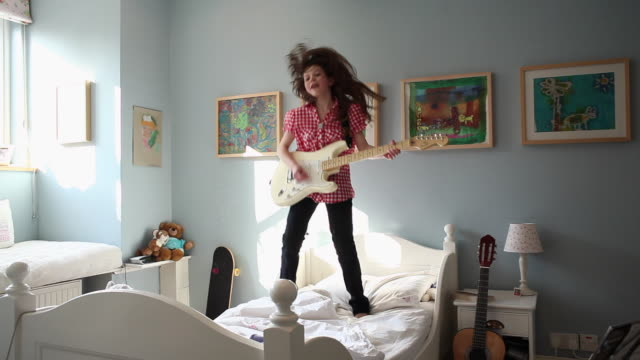 vídeos de stock e filmes b-roll de ws pan girl (10-11) playing guitar and jumping on her bed / perth, western australia, australia - 10 11 anos