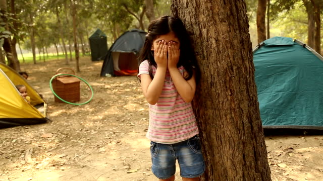 Girl playing hide and seek game in the park, Delhi, India
