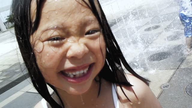 girl playing in a fountain - childhood stock videos & royalty-free footage