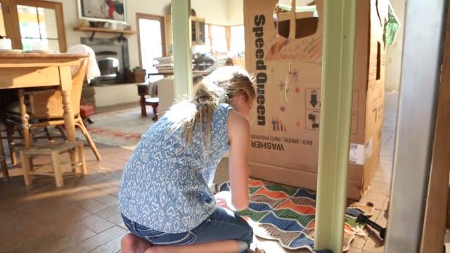 girl playing in card board box