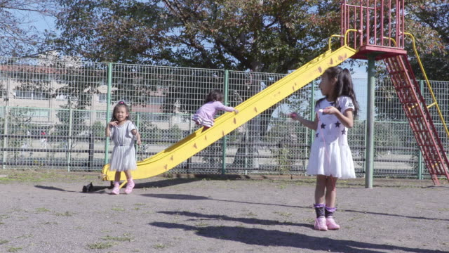 stockvideo's en b-roll-footage met girl playing in the park - glijbaan speeltuintoestellen