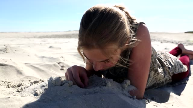 girl playing in the sand - liegen stock-videos und b-roll-filmmaterial