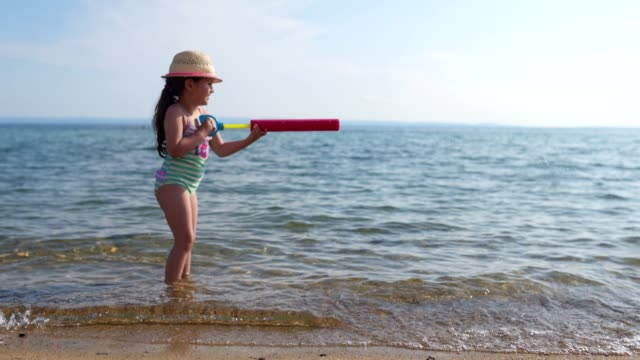 girl playing in the sea - squirt gun stock videos and b-roll footage
