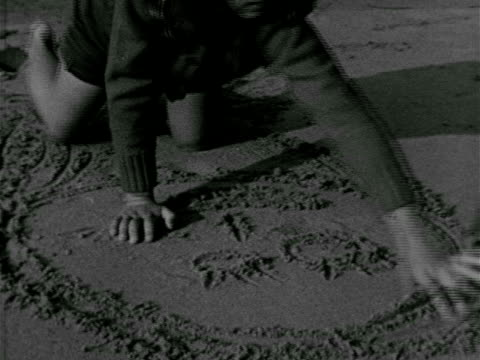BEACH Girl playing in wet sand w/ ocean BG drawing w/ fingers HA TD BEHIND Girl w/ smiling face drawn in sand Play childhood young youth innocence...
