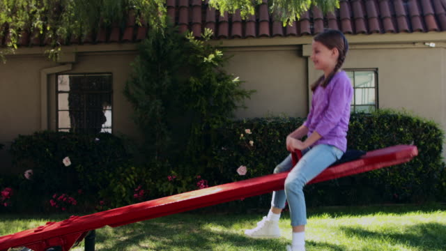 ms girl playing on a seesaw - wippe stock-videos und b-roll-filmmaterial