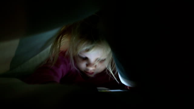 Girl playing on cell phone under duvet