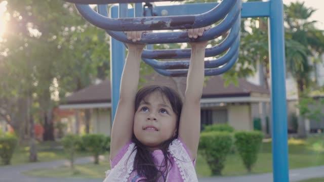 遊び場の機器で遊んで女の子 - ユーラシアエスニシティ点の映像素材/bロール