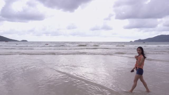 girl playing on the beach in front of the sea - maglietta senza maniche video stock e b–roll