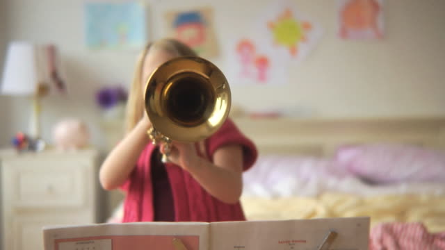 MS R/F Girl (6-7) playing trumpet in bedroom / Jersey City, New Jersey, USA