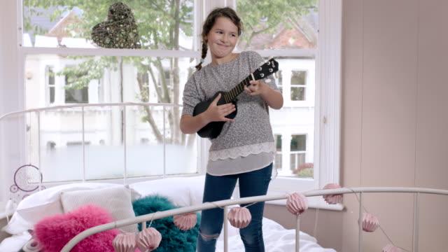 vídeos de stock, filmes e b-roll de girl playing ukulele in her room - ukulele
