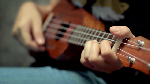 Mädchen spielen wie man ukulele spielt, Nahaufnahme