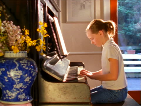 PROFILE PAN girl playing upright piano in living room