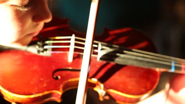 girl playing violin in sunset light