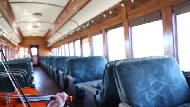 girl playing violin in vintage train car