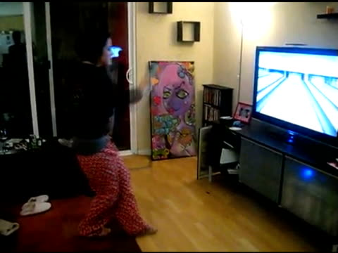 / girl playing wii video game bowling does a victory dance after a strike but falls down after she slips on floor video game victory dance fall on... - wipeout stock videos & royalty-free footage