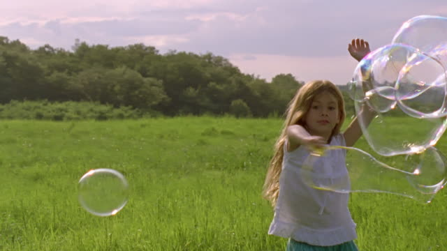 MS, Girl (6-7) playing with bubbles and in field, Chateau du Parc, Saint Ferme, France