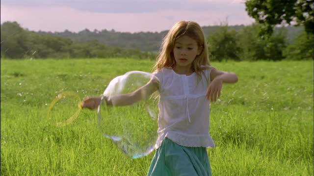 MS, CU, Girl (6-7) playing with bubbles in field, Chateau du Parc, Saint Ferme, France