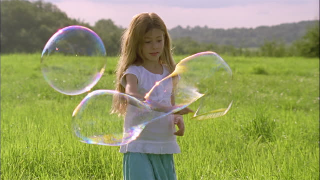ms, pan, girl (6-7) playing with bubbles in field, chateau du parc, saint ferme, france - tre quarti video stock e b–roll
