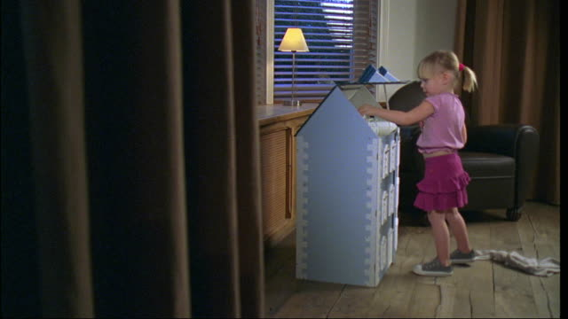 ms, pan, girl (2-3) playing with doll house, brussels, belgium - おもちゃの家点の映像素材/bロール