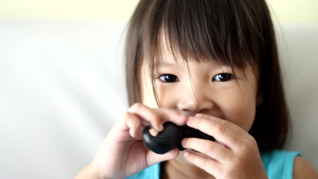 girl playing with fake mustache