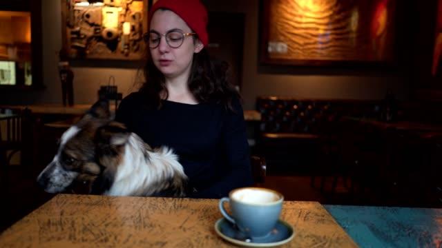 vidéos et rushes de fille jouant avec son chien dans un café de confortables - casquette