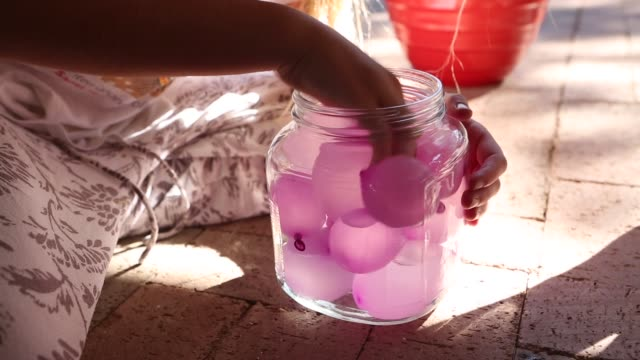 girl playing with little water balloons - girls wearing see through clothes stock videos and b-roll footage