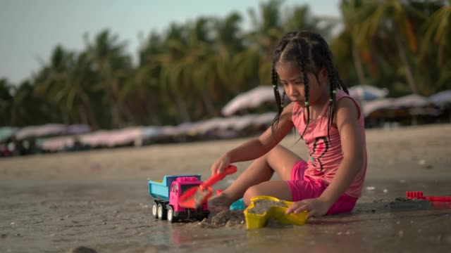 Girl playing with sand and toys at beach