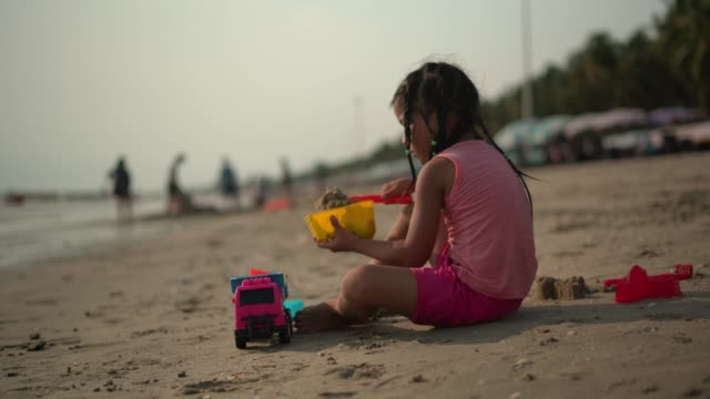 vídeos de stock e filmes b-roll de girl playing with sand and toys at beach - braided hair