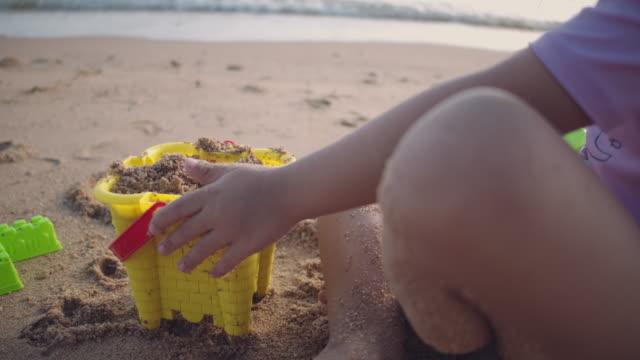 mädchen spielt mit sand am strand - schlossgebäude stock-videos und b-roll-filmmaterial
