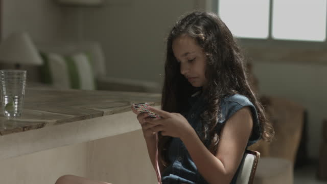 girl playing with smart phone in kitchen - one girl only stock videos & royalty-free footage
