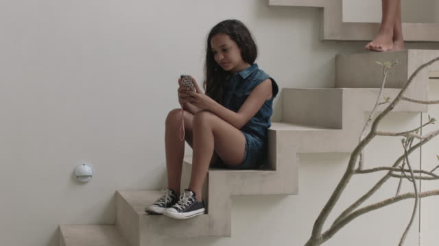 Girl playing with smart phone on stairs mother joins her