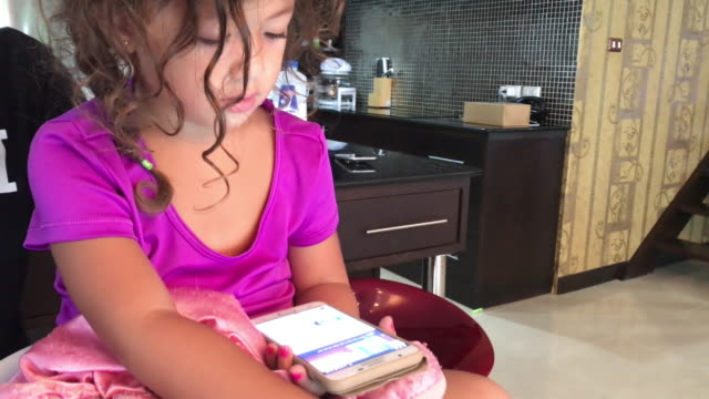 Girl playing with smartphone. 4K
