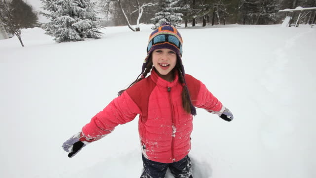 WS Girl playing with snow during snowstorm / Yarmouth, Maine, USA